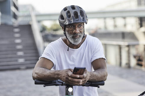Portrait of pensive mature man wearing cycling helmet leaning on handlebar of Electric Scooter - FMKF05901