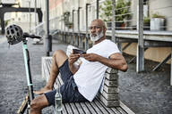Portrait of mature man with E-Scooter and cell phone sitting on bench in summer - FMKF05904