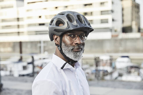 Portrait of mature businessman with grey beard wearing cycling helmet and glasses - FMKF05907