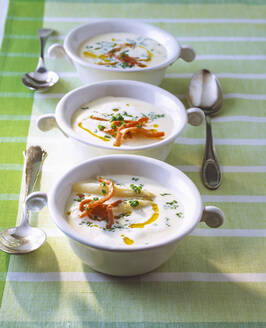 Asparagus soup with chervil and ham in bowls on table - PPXF00254