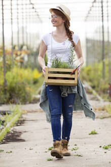 Beautiful young woman holding wooden box with plants in the greenhouse - JSRF00512