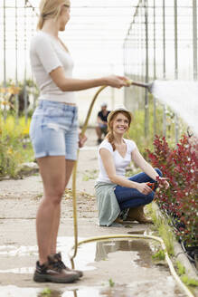 Two young women taking care and watering flowers with hose in the greenhouse - JSRF00524