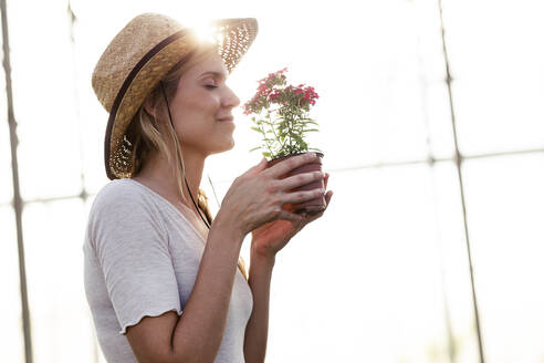 Beautiful young woman smelling at flower in the greenhouse - JSRF00548