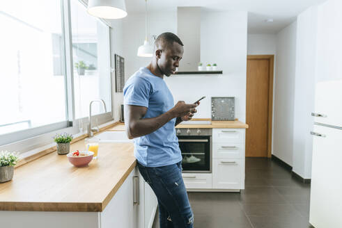 Young man using cell phone in kitchen at home - KIJF02596