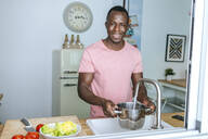 Portrait of smiling young man pouring water into pot in kitchen - KIJF02605