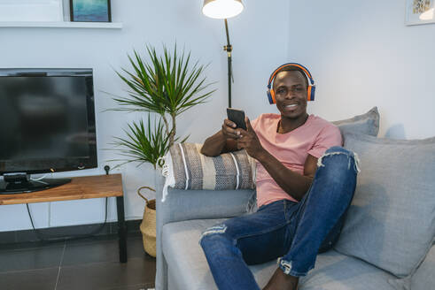 Portrait of smiling young man with headphones and smartphone on couch at home - KIJF02611