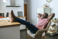 Young man sitting relaxed in the kitchen at home - KIJF02614