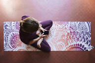 Young brunette woman practising yoga, using smartphone - IGGF01291