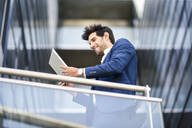 Smiling businessman using tablet on balcony of an office building - JSMF01230