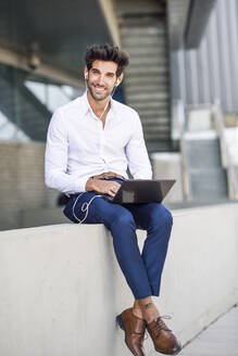 Smiling businessman wearing earphones using laptop outdoors in the city - JSMF01236