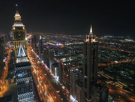 Aerial view of illuminated skyscrapers at night in Dubai, United Arab Emirates. - AAEF03332