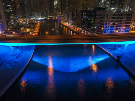 Aerial view of an illuminated bridge on the canal of Dubai at night, United Arab Emirates. - AAEF03341