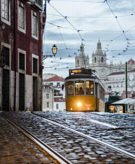 Romantic atmosphere in the old streets of Alfama with the castle in the background and tram number 28, Lisbon, Portugal, Europe - RHPLF01385