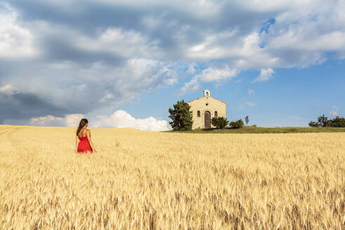 Woman in red dress admiring Notre-Dame-de-Sante chapel in a wheat field, Entrevennes, Alpes-de-Haute-Provence, Provence-Alpes-Cote d'Azur, France, Europe - RHPLF01496