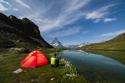 Hiker beside tent looking towards the Matterhorn from lake Riffelsee, Zermatt, canton of Valais, Swiss Alps, Switzerland, Europe - RHPLF01652