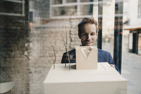 Smiling businessman with architectural model - GUSF02396