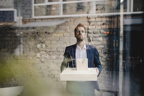Portrait of businessman holding architectural model - GUSF02399