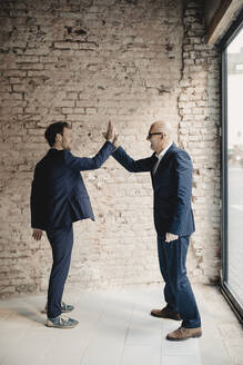 Senior and mid-adult businessman high fiving - GUSF02405
