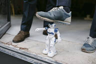 Close-up of businessman stepping on robot - GUSF02420
