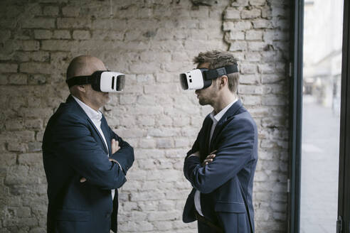 Senior and mid-adult businessman wearing VR glasses - GUSF02423