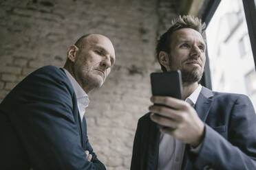Mid-adult businessman holding cell phone with  senior businessman behind him - GUSF02426