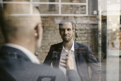 Portrait of mid-adult businessman and senior having a meeting - GUSF02435