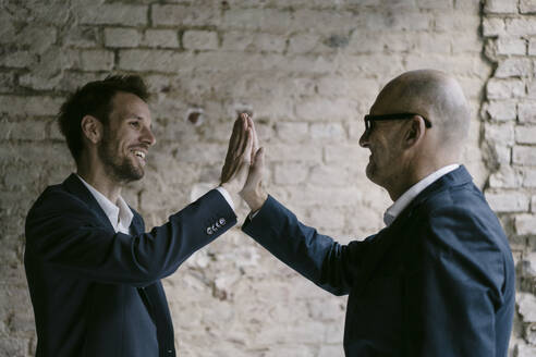 Senior and mid-adult businessman high fiving - GUSF02438