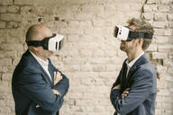Senior and mid-adult businessman wearing VR glasses - GUSF02444