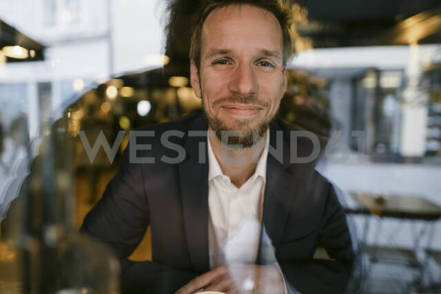 Portrait of smiling businessman behind windowpane - GUSF02450 - Gustafsson/Westend61