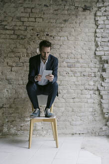 Businessman sitting on chair using tablet - GUSF02456