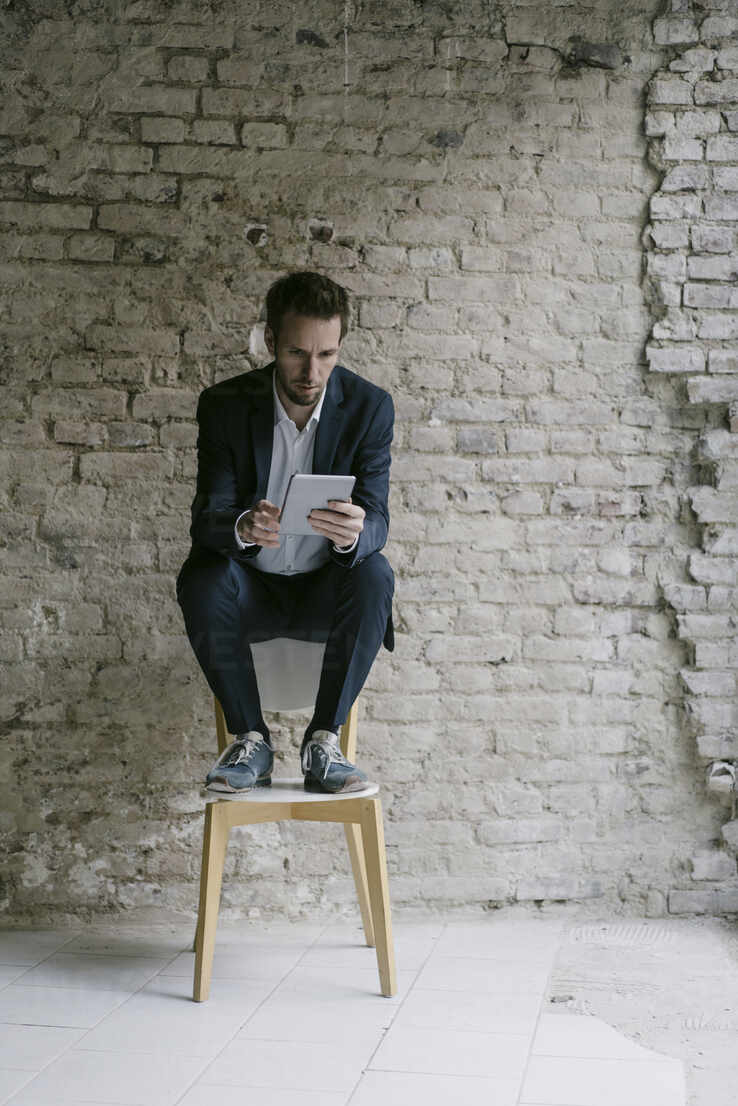 Businessman sitting on chair using tablet - GUSF02456 - Gustafsson/Westend61