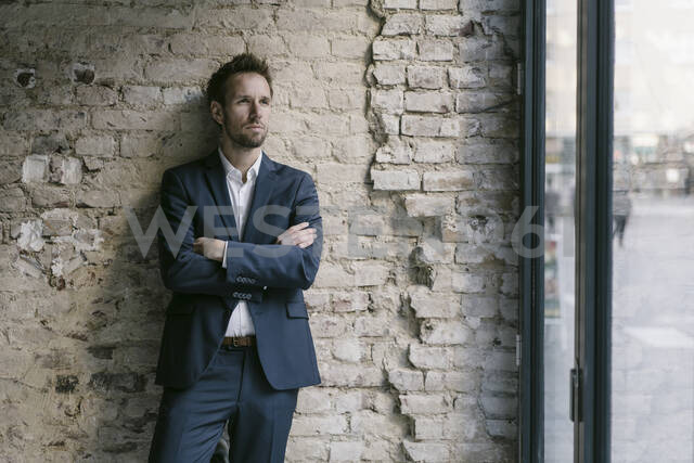 Portrait of businessman leaning against brick wall - GUSF02459 - Gustafsson/Westend61