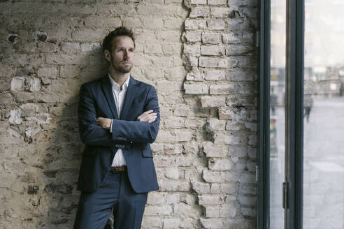 Portrait of businessman leaning against brick wall - GUSF02459