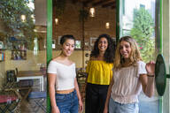 Portrait of three smiling young women at a cafe - MGIF00661
