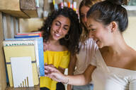 Three smiling young women at a bookshelf - MGIF00664