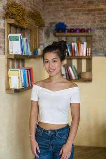 Portrait of smiling young woman at bookshelf - MGIF00667