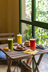 Variation of smoothies and cake on wooden table - MGIF00670