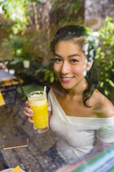 Portrait of smiling young woman holding a healthy drink behind glass pane - MGIF00682