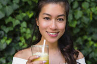 Portrait of smiling young woman holding a healthy drink - MGIF00685