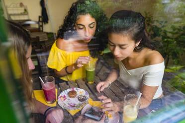 Three young women with smoothies meeting in a cafe sharing smartphone - MGIF00688