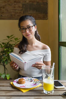 Portrait of smiling young woman sitting at table with a book - MGIF00694