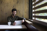 Man smiling using a tablet in a cafe in Madrid, Spain. - ABZF02431