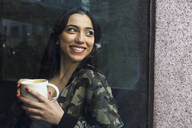 Young woman sitting in cafe with cup of coffee and looking out of window - ABZF02476