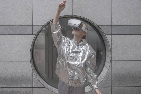 Girl in silver suit looking through VR goggles, watching her hand - VPIF01432