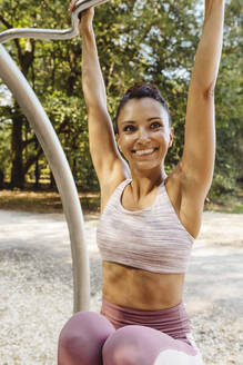 Smiling woman lifting herself up on a fitness trail - MFF04777