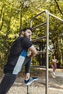 Man stretching on fitness trail - MFF04792