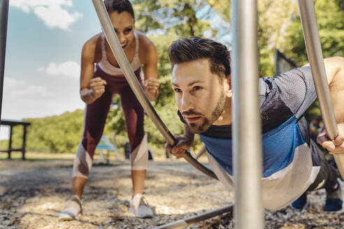 Woman supporting man doing press-ups on a fitness trail - MFF04801