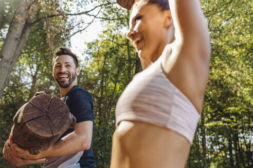 Man watching happy woman lifting up heavy logs on a fitness trail - MFF04804