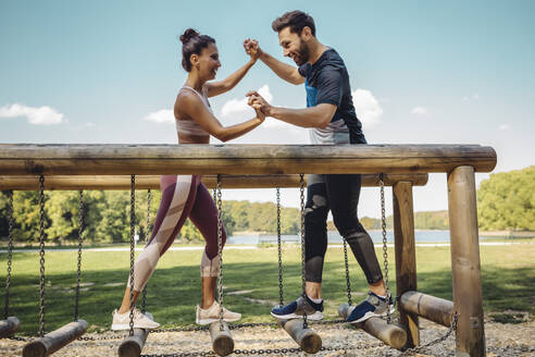 Man and woman playfighting on balance logs on a fitness trail - MFF04810