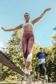 Woman balancing on slackline on a fitness trail - MFF04819